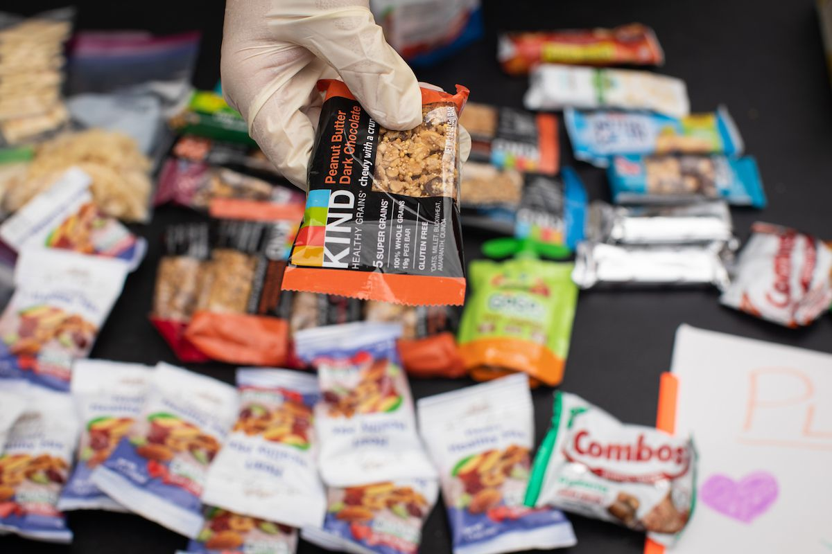 An outstretched hand extends a Kind granola bar, while other out-of-focus granola bars are visible in the background of the photo