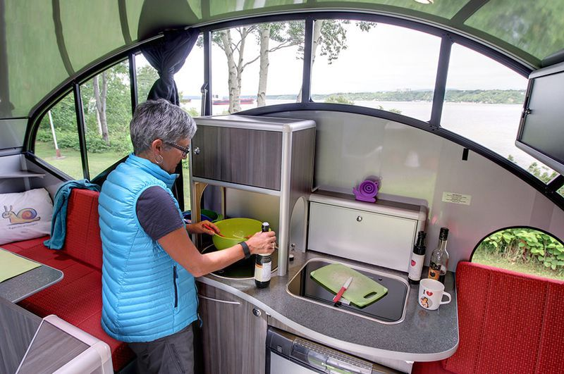 The interior of a camper trailer. There is a woman in a blue vest who is stirring food in a bowl on a kitchenette.