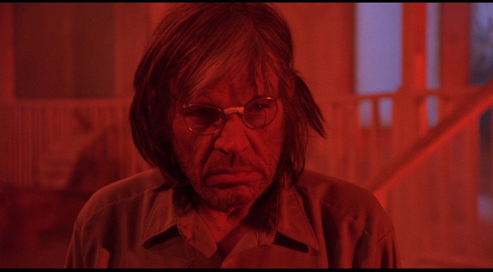 a grizzled man in glasses grimaces in a bath of red light