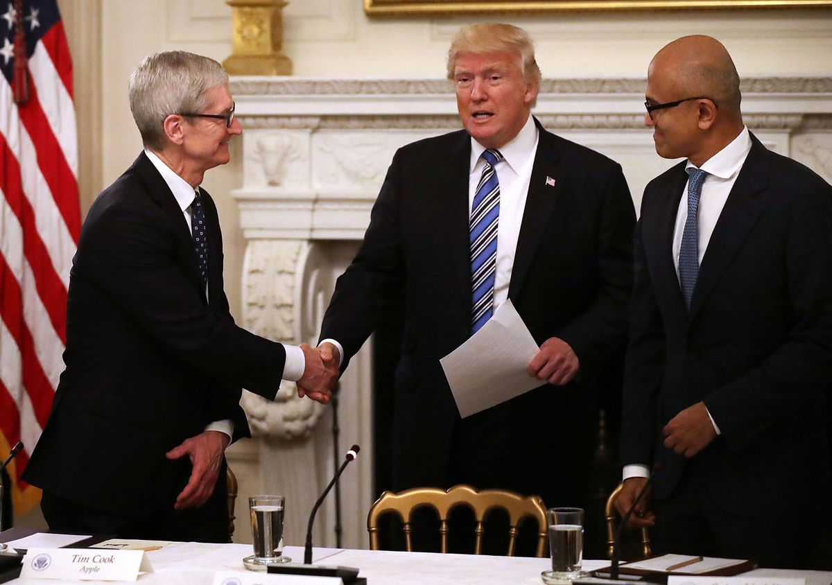 Apple CEO Tim Cook, President Donald Trump and Microsoft CEO Satya Nadella shake hands at the White House.