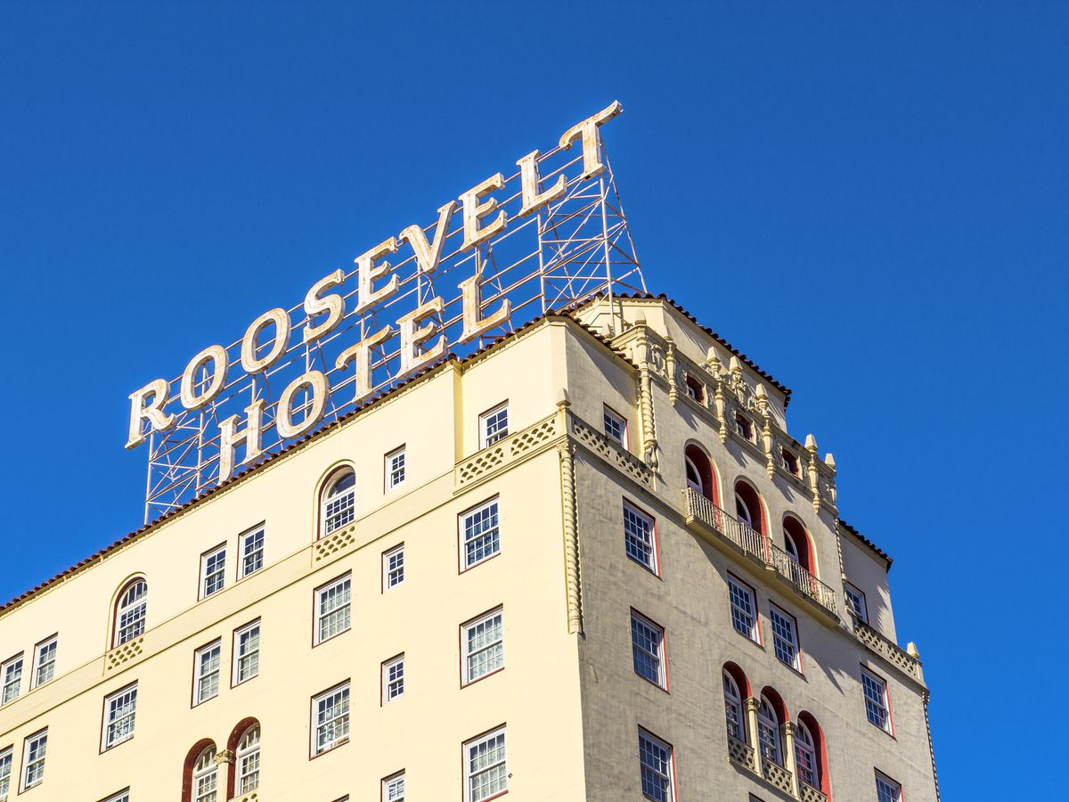 """A tall, white-colored building with a large sign on top that says """"Roosevelt Hotel"""""""