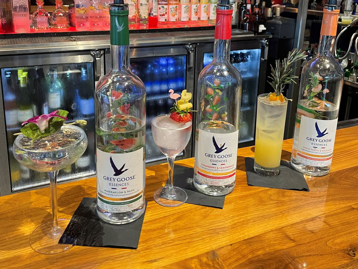 Three cocktails alternating with three Grey Goose Essences liquor bottles on a wooden bar. The cocktails are topped with flowers, rosemary, and fruit garnishes