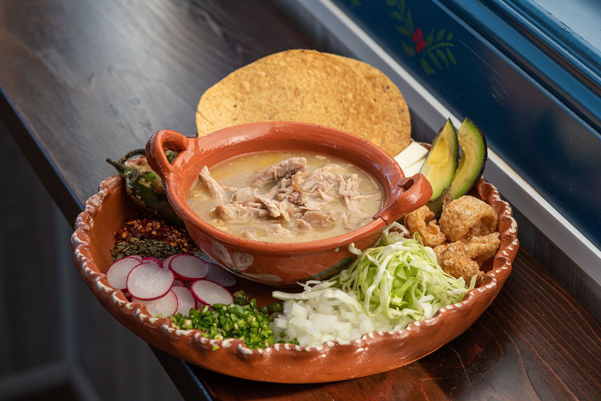 Green pozole with toppings to the side.