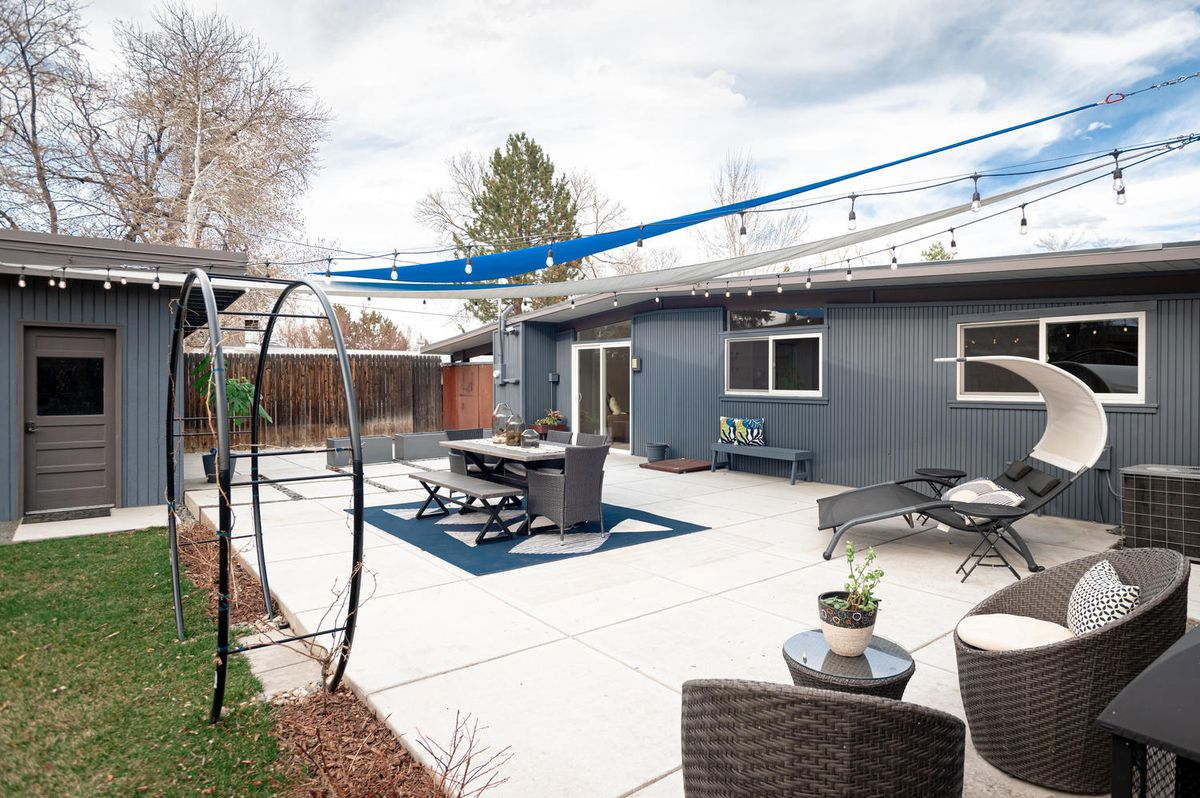 A backyard has a lounge and dining area with shade and patio lights strung above.