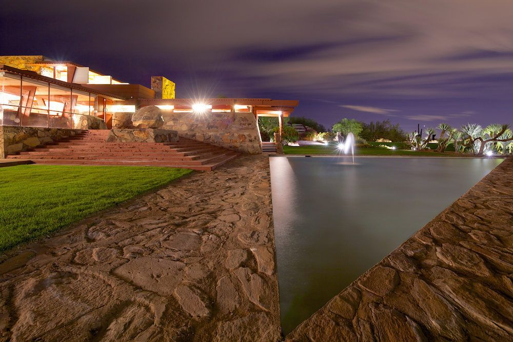 The exterior of Frank Lloyd Wright's Taliesin West. In the foreground is a stone fountain. In the distance is a house with a staircase and stone facade. The house has floor to ceiling windows.