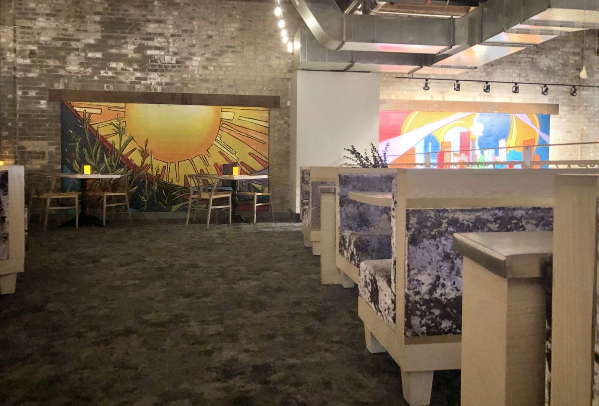 Banquettes upholstered with lavender velvet line the right side of the lofted space. A red, yellow, and orange sun mural dominates the brick wall at the center, back of the room. Two two top tables are placed in front of it.