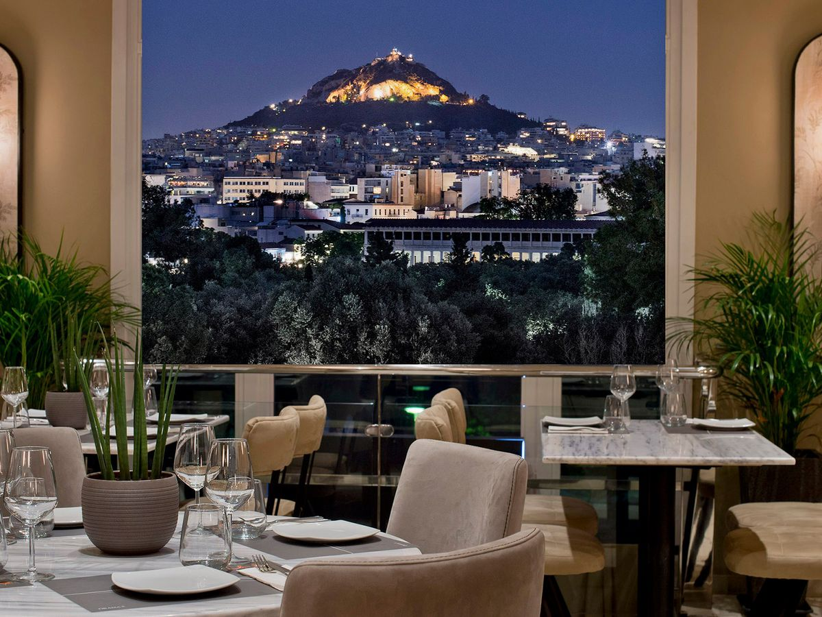 A luxe restaurant interior with tables set for dinner. Outside the large windows is a view of Athens at night and the Acropolis, lit up in the distance