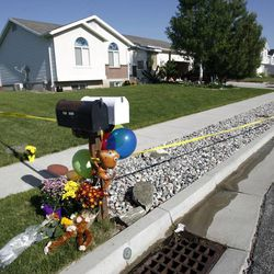 Flowers and stuffed animals are placed at the crime scene in West Point on Thursday, May 23, 2013. Two young brothers were found dead in their West Point home late Wednesday. Their 15-year-old brother was booked into the Farmington Bay Youth Detention Center Thursday in connection with the deaths.