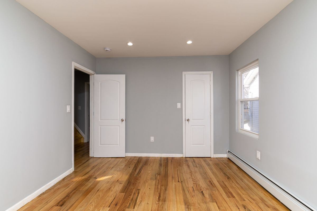 A bedroom with hardwood floors, grey walls, and a small window.