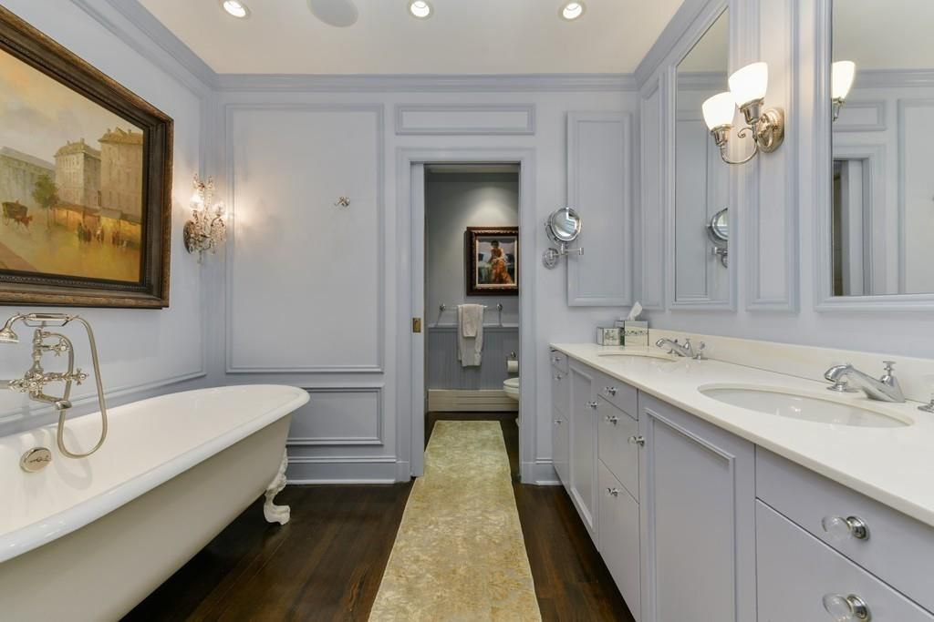 A large bathroom with a long double vanity, a soaking tub, and a small separate room for the toilet.