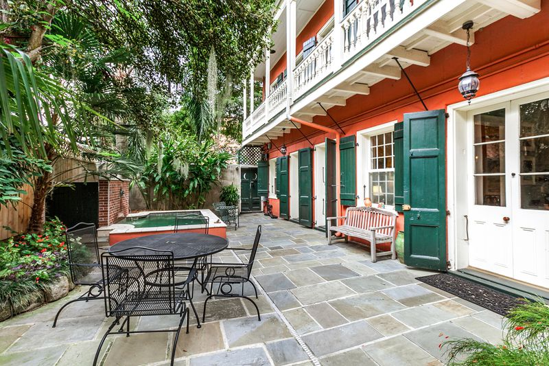 Traditional New Orleans courtyard with fountain, slate floors and greenery, overlooked by a balcony