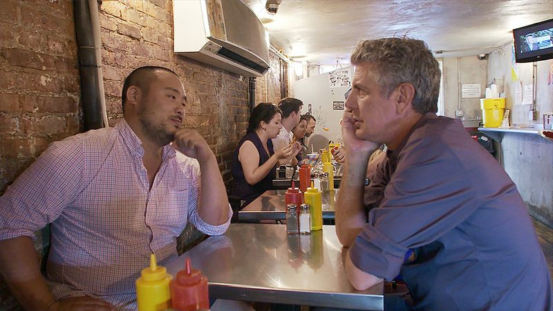 The two chefs and friends sit at an East Village hot dog joint.