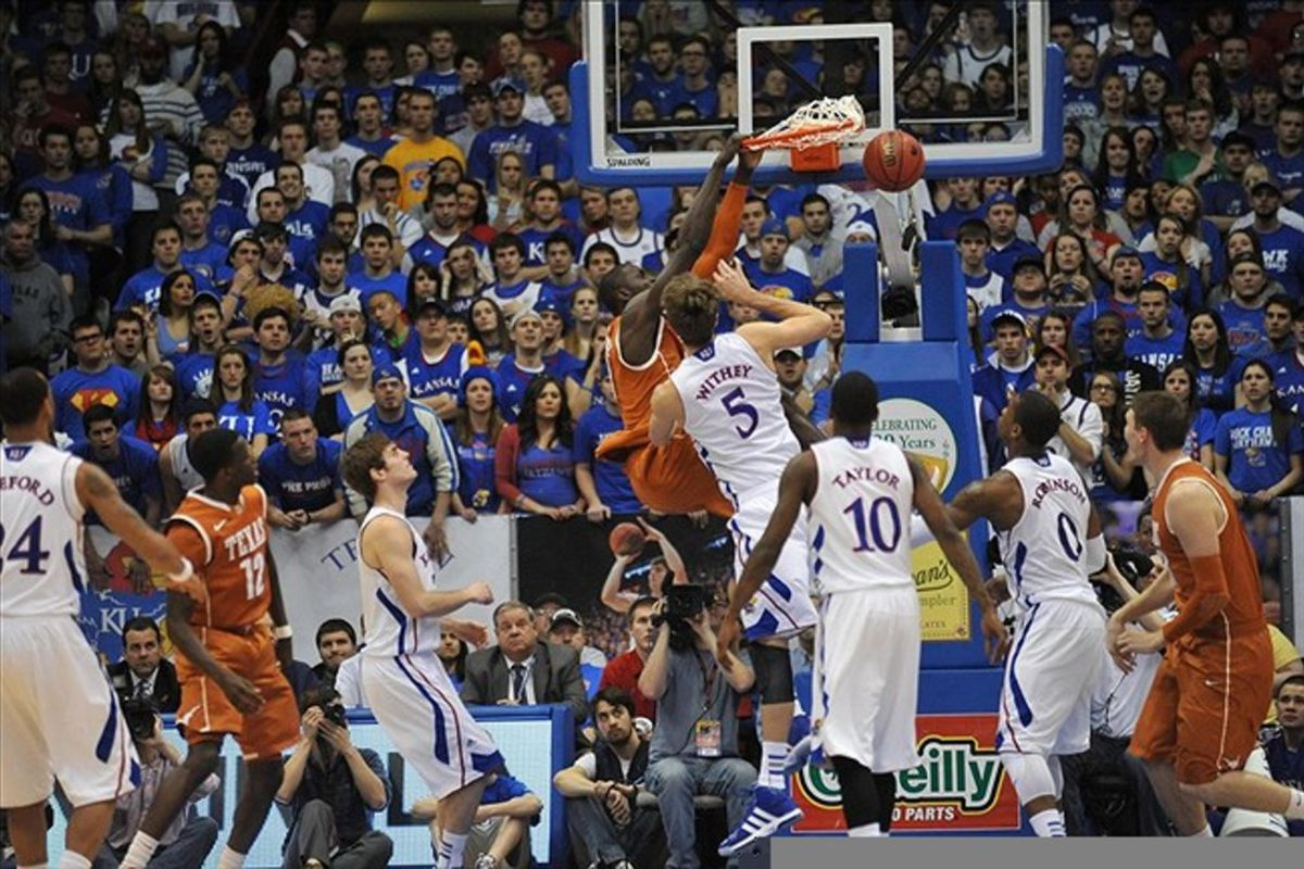 March 03, 2012; Lawrence, KS, USA; Texas Longhorns forward/center Alexis Wangmene (20) dunks the ball as Kansas Jayhawks center Jeff Withey (5) defends in the first half at Allen Fieldhouse. Mandatory Credit: Denny Medley-US PRESSWIRE