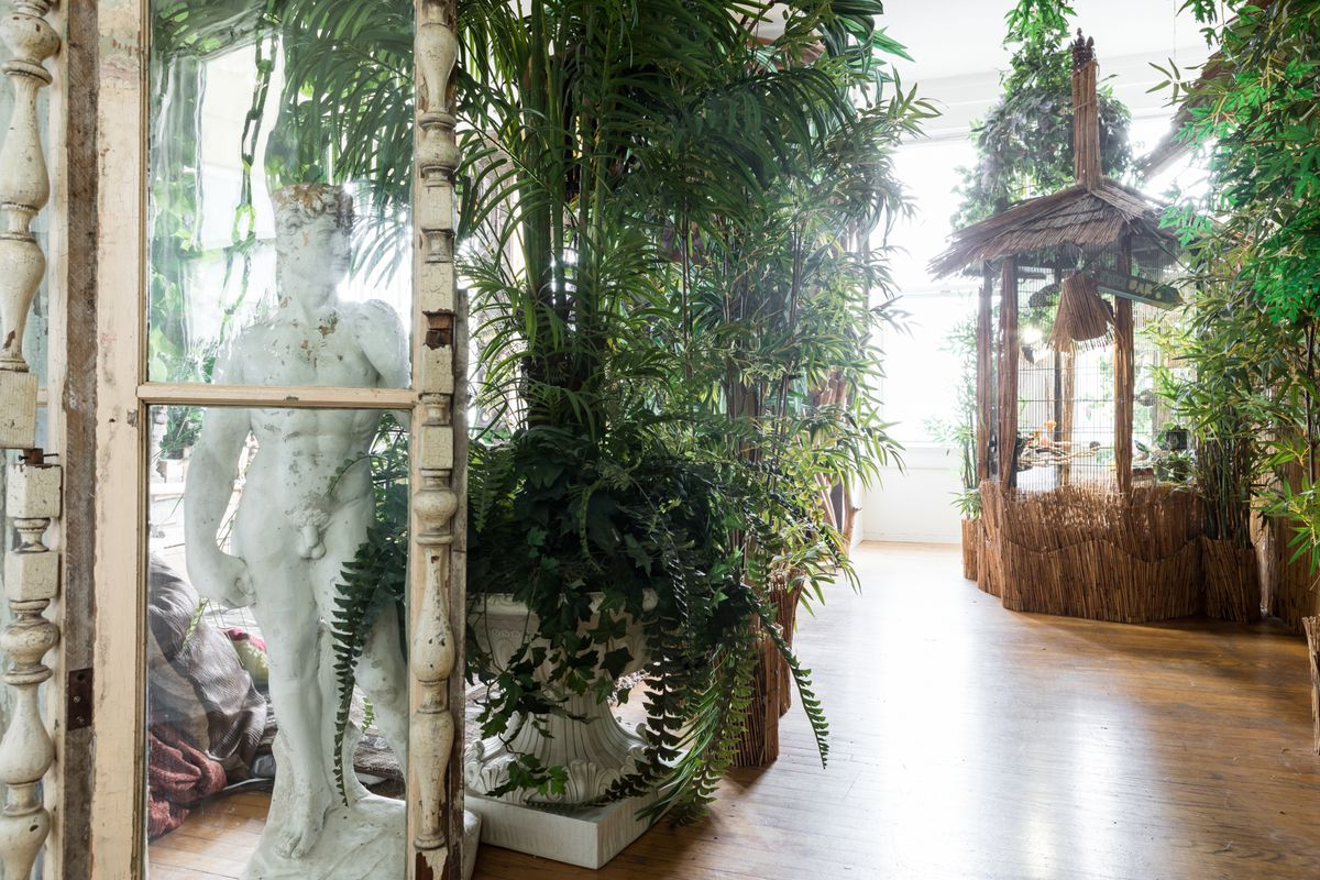 An interior living space with many plants in planters and a straw hut. There is a window in the foreground. Behind the window is a tall statue of a nude male.