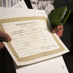 Gregory Enke holds up his marriage certificate at the Salt Lake County Clerk's Office in Salt Lake City, Monday, Oct. 6, 2014.