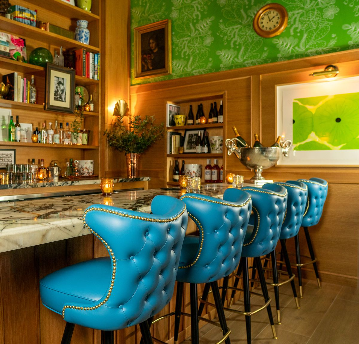 Light blue bar seats at a dark bar with green print and vintage touches and art.