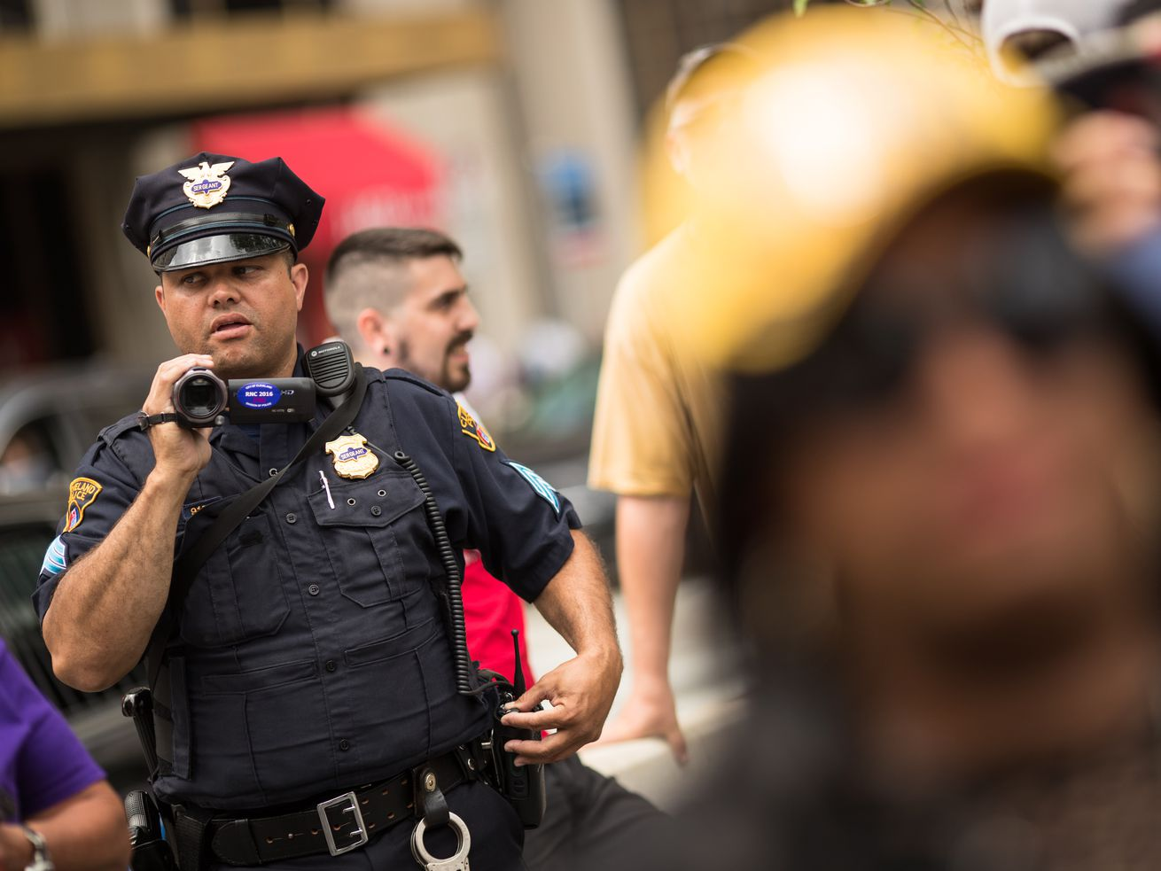 A police officer holds a camera and looks at a crowd.
