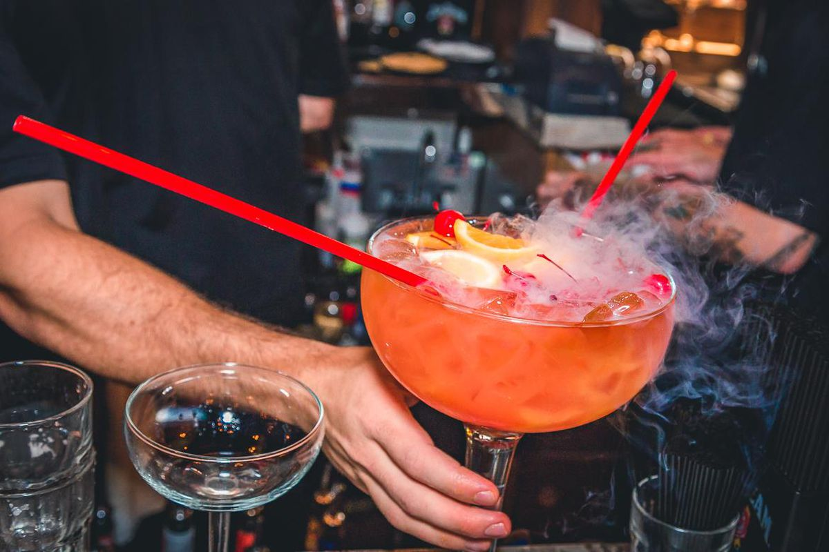 A bartender holds a pink scorpion bowl in a giant glass. It has two straws coming out of it.