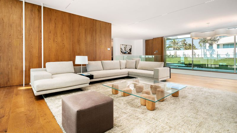A living room with  modern beige sofas and wood paneled walls. A glass coffee table sits on wooden blocks.