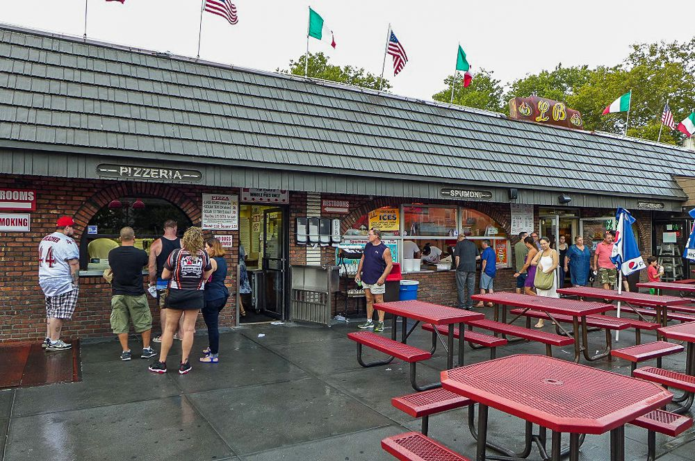 L & B Spumoni Gardens's outdoor area has people lined up at a counter, with red tables.