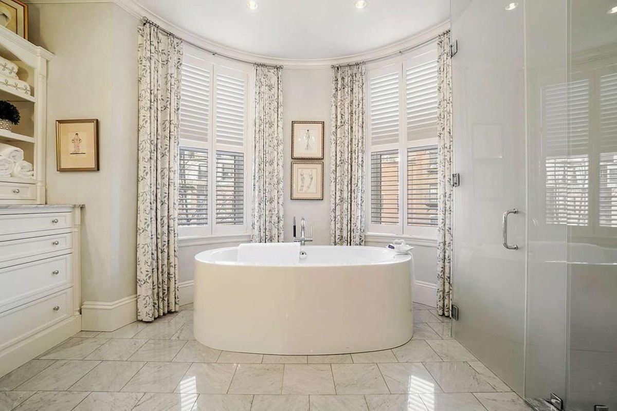 A spacious bathroom with a soaking tub prominently positioned in front of large windows.