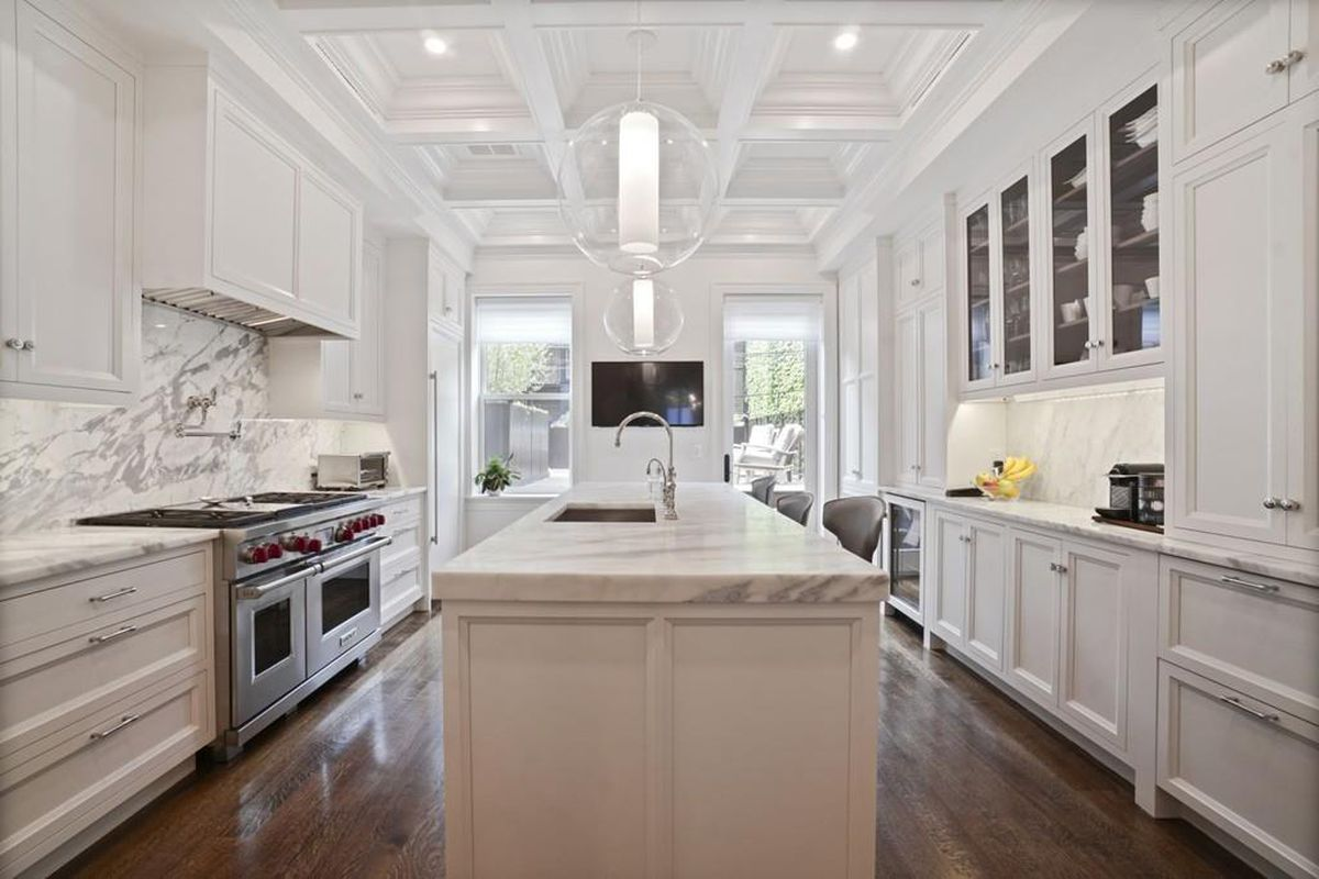 A spacious kitchen with two ovens and a large marble island.