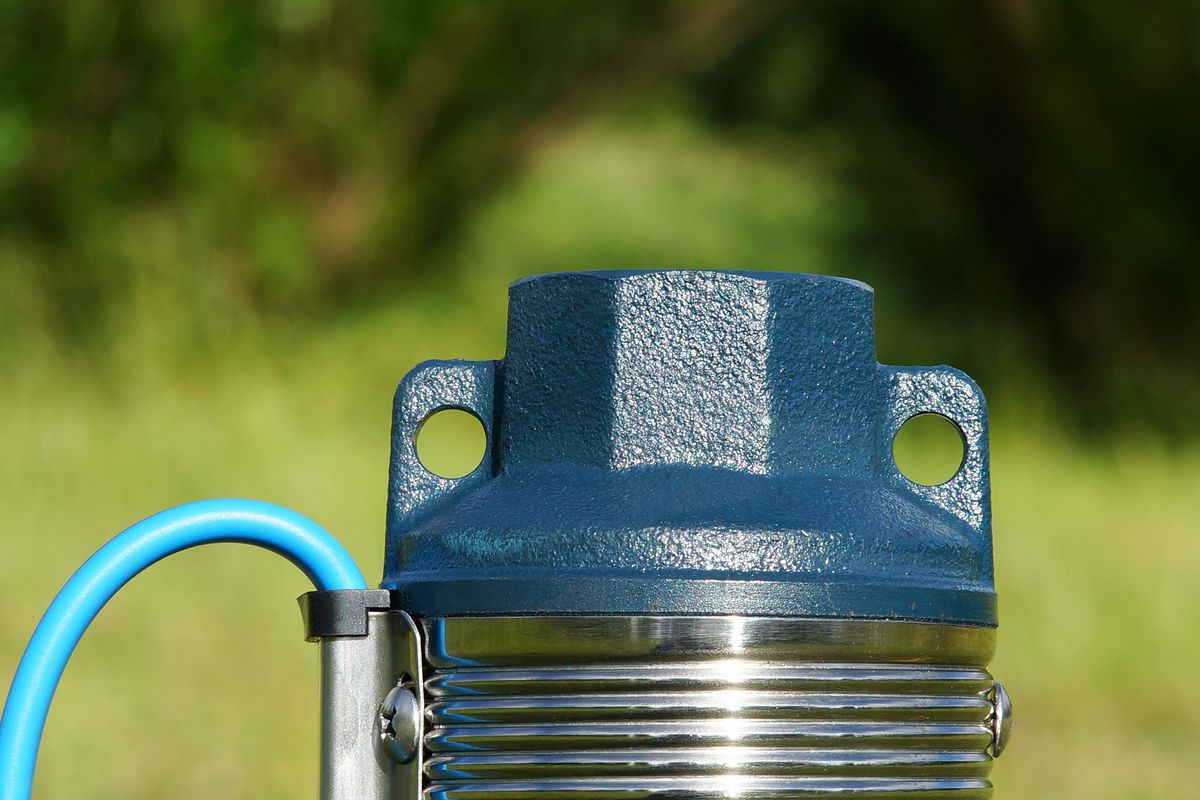 A well pump with blue cap and silver fixtures.