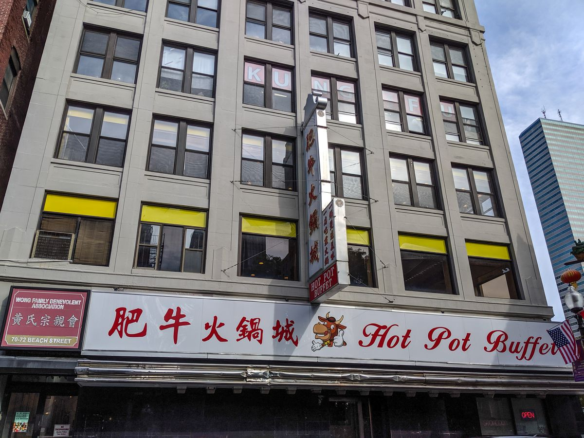 Signage for Hot Pot Buffet in Boston's Chinatown — red text on a white background, with an image of a cartoonish smiling bull giving a thumbs up