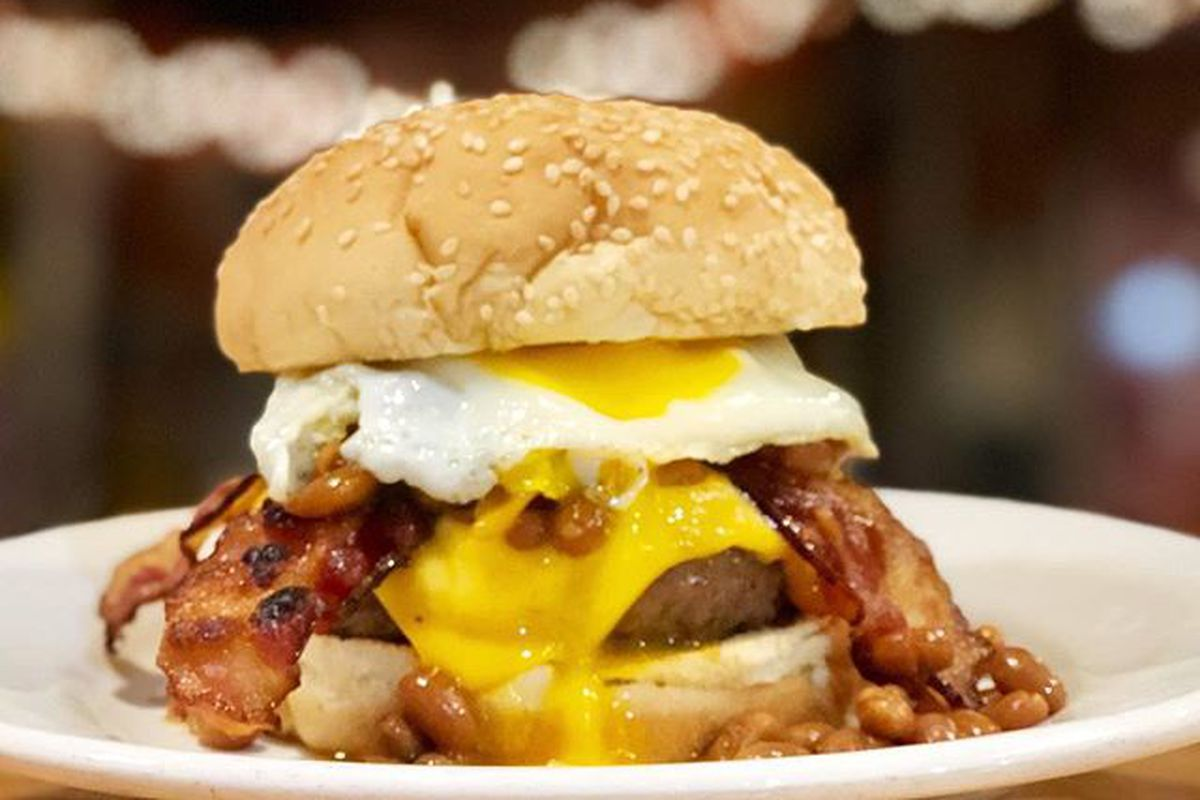 A burger on a sesame bun. It's topped with bacon, egg, and cheese.