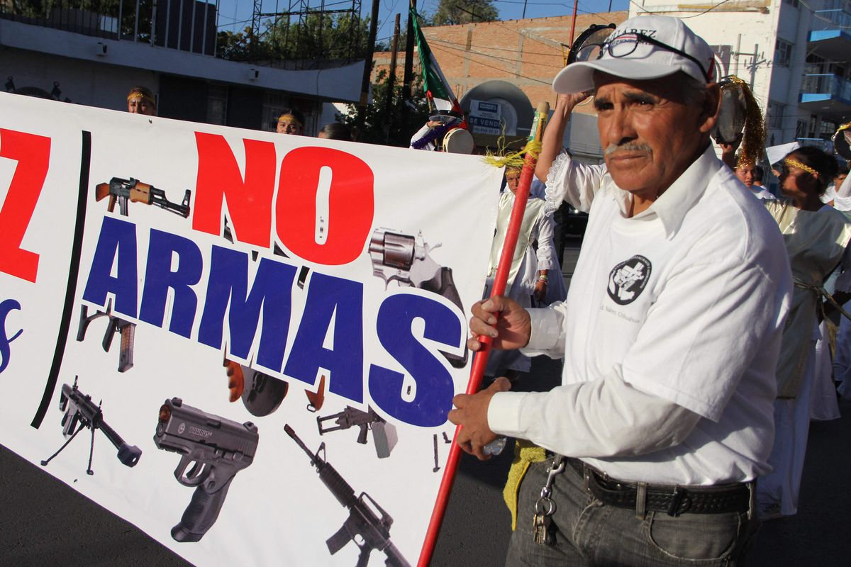 """A man holds a sign calling for """"No weapons"""" during a march for peace and against violence in Ciudad Juarez. """"We are going to win the trial, and we are going to drastically reduce illicit arms trafficking to Mexico,"""" Foreign Minister Marcelo Ebrard says of a lawsuit filed by Mexico's government against U.S. gun makers and distributors."""