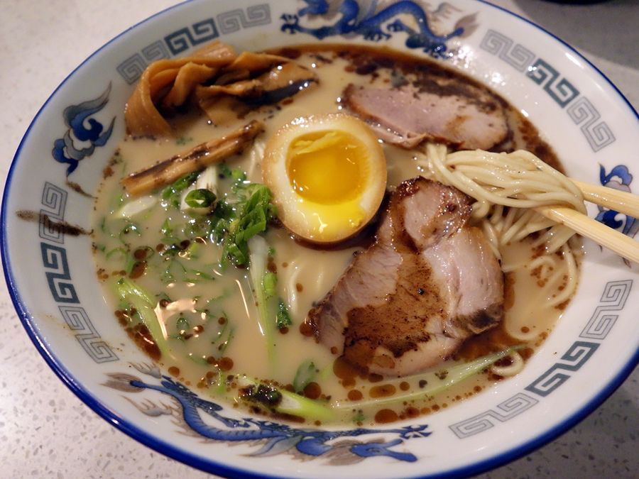 Shoyu pork ramen in a white and blue bowl topped with egg.