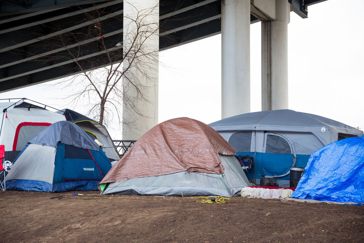 Several tents under a freeway overpass