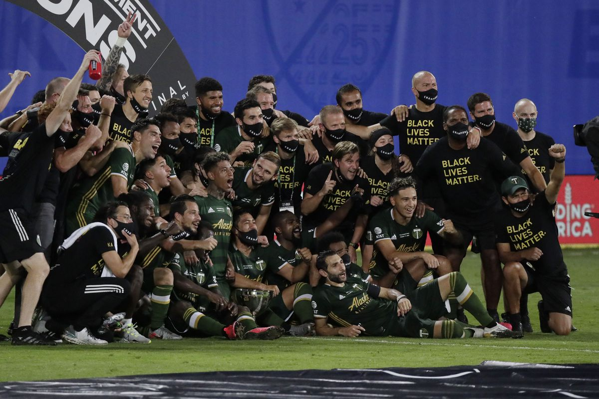 Portland Timbers players pose for photos after defeating Orlando City 2-1 in the MLS is Back tournament championship match.