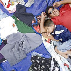 Gabino Rosas and his 6-year-old son, Angel, rest under the tent where they are selling clothing Sunday at the Swap Meet in West Valley City. The swap meet is held on Saturdays and Sundays.