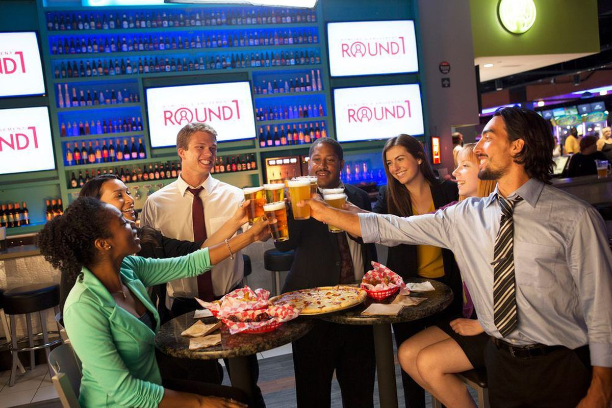 A group of friends raise their beer glasses for a toast at the all-ages arcade and games center.