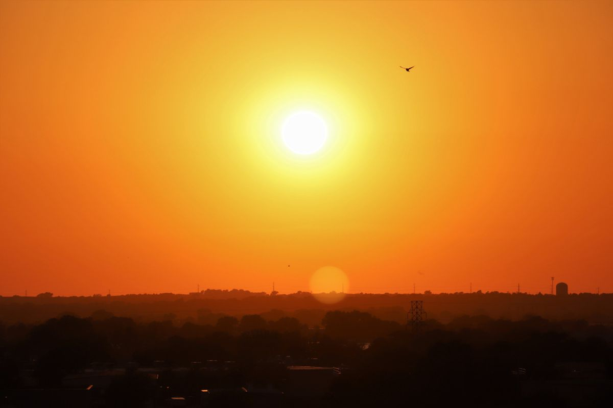 The sun rising over a flat landscape in an orange sky.