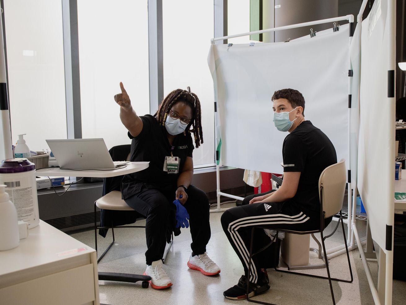 Henrietta Nkemeh talks to Christian Clettenberg, 15, before inoculating him with a COVID-19 vaccine at the Rush University Medical Center in the Illinois Medical District, Thursday morning, May 13, 2021. Kids as young as 12 became eligible for the COVID-19 vaccine Thursday.   Pat Nabong/Sun-Times
