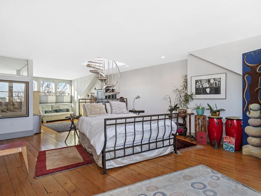 A top-floor bedroom that encompasses an entire floor, and there's a winding upward staircase behind the bed.