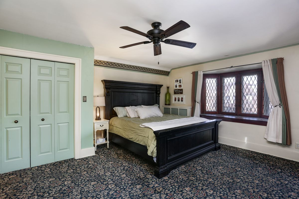 The room has a large bed and dark wood headboard on floral carpet. The bed is next to the row of leaded glass windows with wood trim.