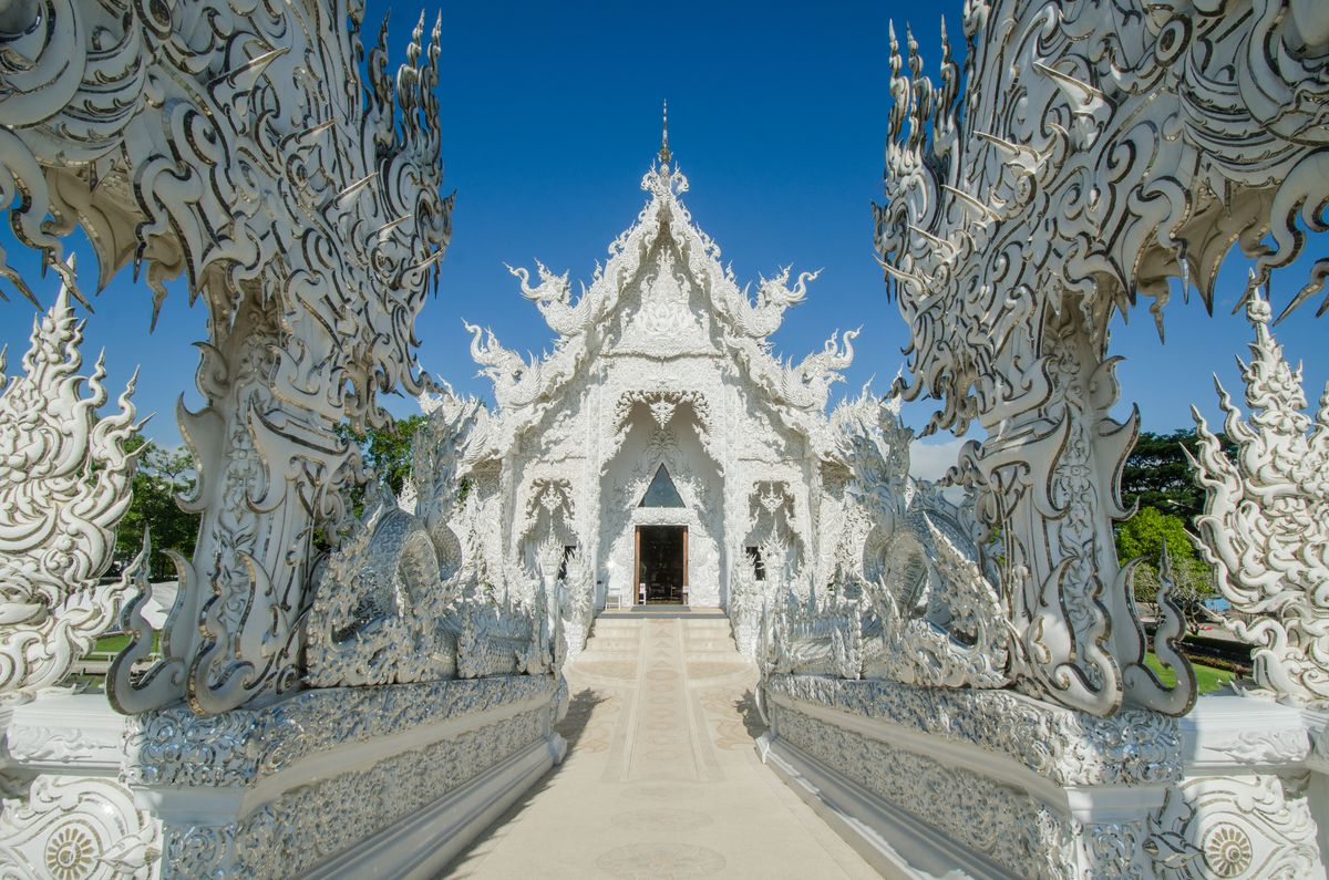 """The exterior of <span data-author=""""843"""">Wat Rong Kuhn in Thailand. The facade and surrounding structures are white and ornately decorated.</span>"""