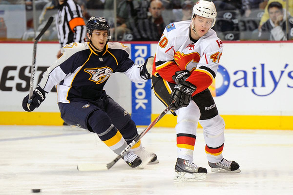 NASHVILLE TN - FEBRUARY 01:  Alex Tanguay #40 of the Calgary Flames passes the puck past Marcel Goc #9 of the Nashville Predatorson February 1 2011 at the Bridgestone Arena in Nashville Tennessee.  (Photo by Frederick Breedon/Getty Images)