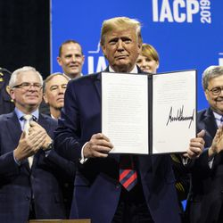 President Donald Trump signs an executive order establishing the Commission on Law Enforcement and the Administration of Justice after speaking at the International Association of Chiefs of Police convention at McCormick Place, Monday morning, Oct. 28, 2019.