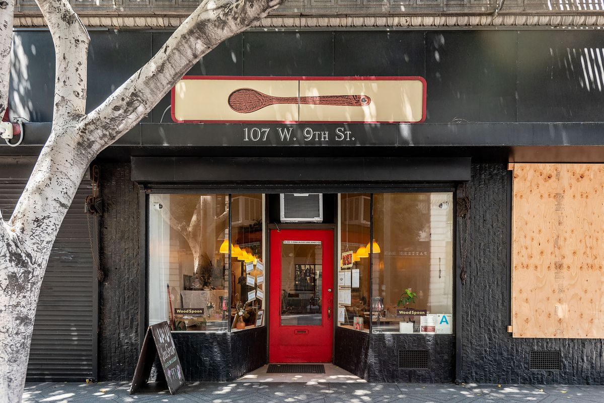 Outside Wood Spoon, a Brazilian restaurant in Downtown LA with black painted storefront, red door, glass windows.