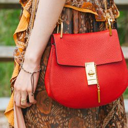 A bright bag warmed up her dress's muted tones.