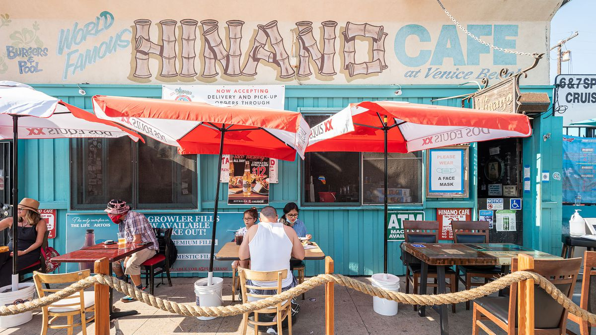 A collection of diners sit outside in front of a pastel blue dive bar along the beach.
