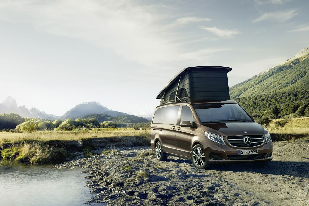 A brown van, the Mercedes Marco Polo. It has an inflatable tent on the roof. The van is parked in a field. There are mountains in the distance.