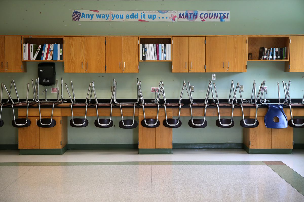 Chairs placed on top of a bench in an empty classroom.