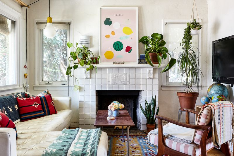 A white-walled living room with white tiled fireplace. A large artwork featuring fruits on a pale pink background hangs above. A white leather sofa fits snugly in one corner. There are plants on the fireplace mantel and hanging from the ceiling.