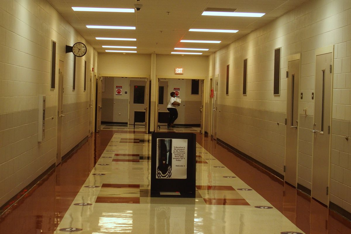 A teacher crosses an otherwise empty hallway with stickers on the floor promoting social distancing