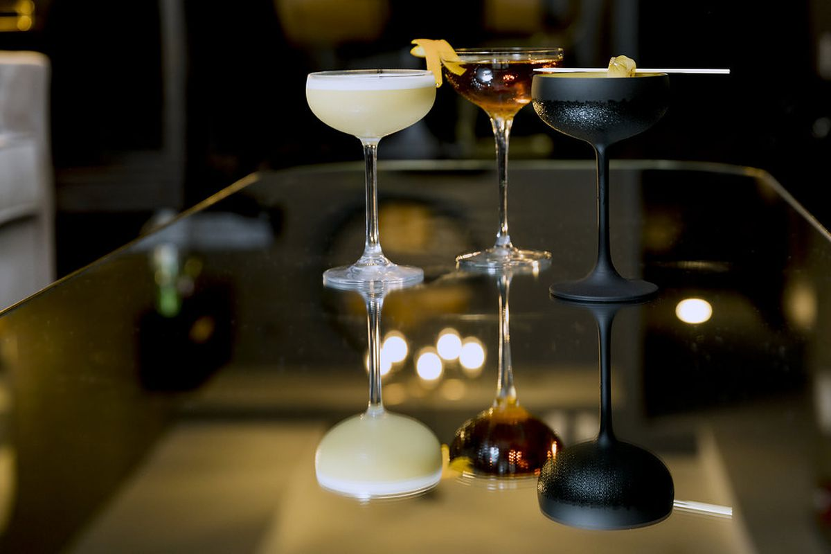A line of three elegant cocktails on a mirrored surface and dark background at Better Sorts Social Club in Boston
